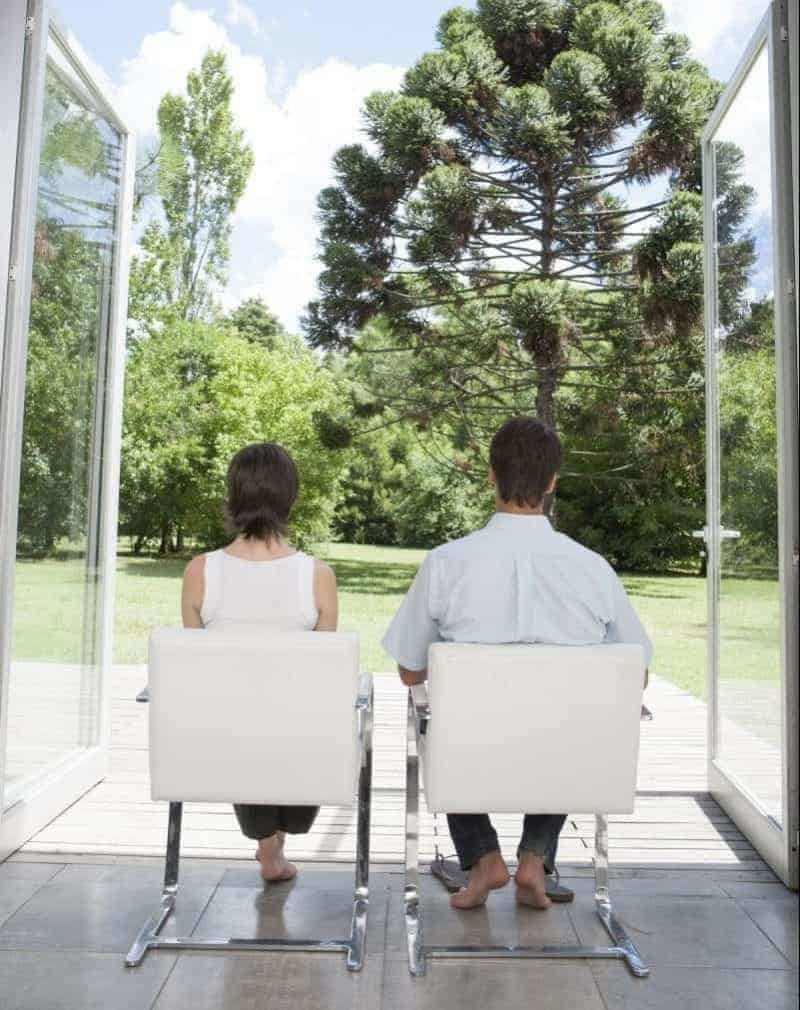 man and a woman sitting in white chairs looking outside to trees through glass doors