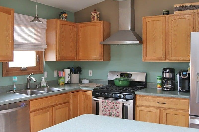 clean kitchen with orange wood cabinets and green counters and walls
